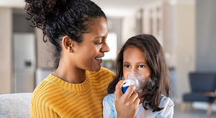 A mother holds an inhaler for her daughter, illustrating the need to enhance patient adherence to asthma therapy